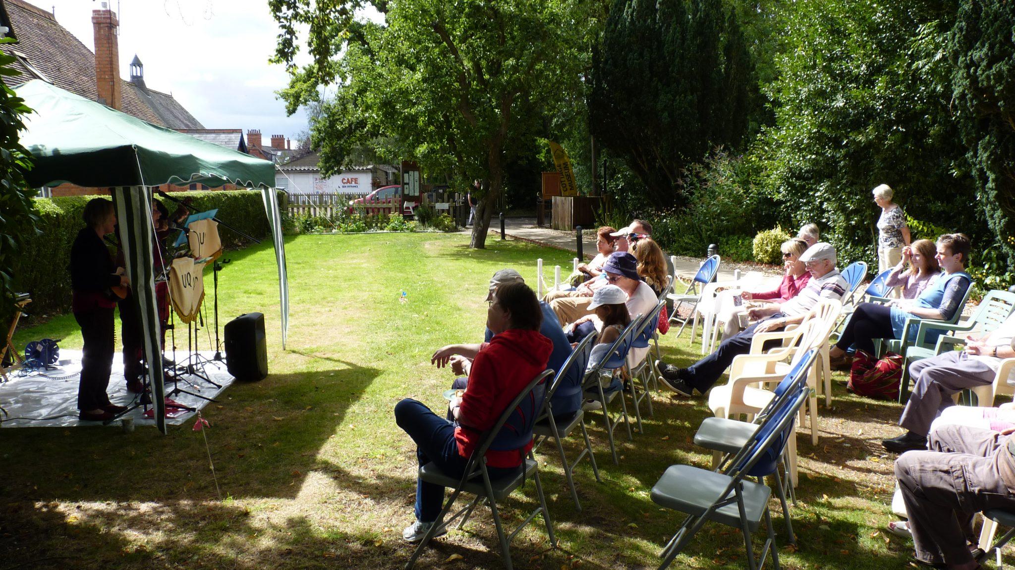 Visitors enjoying the sunshine and music.